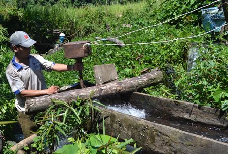 Anh Phạm Văn Run bên chiếc tua-bin dưới suối Niên.             Ảnh: Ý THU